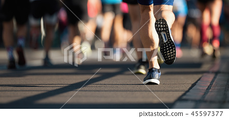Marathon runners running on city road 45597377