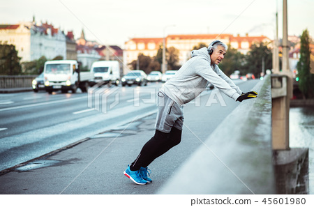 Mature male runner with headphones stretching outdoors on the bridge in Prague city. 45601980