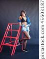 Fashionable brunette beautiful woman posing in studio wearing short jeans. 45603187