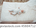 Newborn baby dressed in a suit on a soft bed in the studio. 45604712