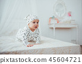 Newborn baby dressed in a suit on a soft bed in the studio. 45604721