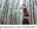 Women stretching arms and breathing fresh air in middle of pinew 45606967