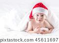 Baby boy with santa hat on bed under white duvet. 45611697