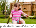 A cute young girl having fun riding a tricycle 45626523