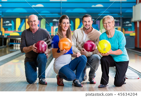 Family with multi colored bowling ball posing 45634204