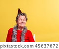 Portrait of a senior woman in studio on a yellow background. Party concept. 45637672