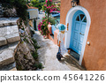 Travel tourist woman on vacation in Greece. Person with blue sunhat in front of traditional 45641226
