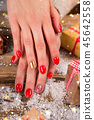 Woman with beautiful red nails on vintage wooden table 45642558