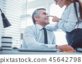 Female worker touching nose of her superior 45642798