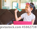 Smile child girl holding airplane paper  45662738