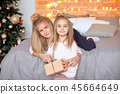 Merry Christmas and Happy Holidays.Cheerful cute children opening gifts. Kids having fun near tree 45664649