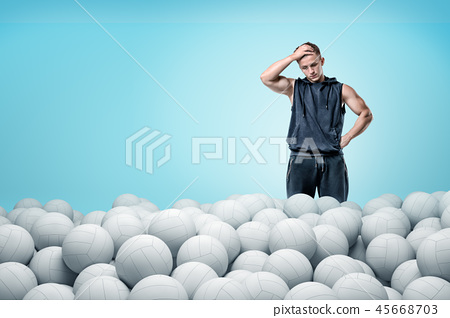 Sport man thinking over white volleyball balls on blue background 45668703