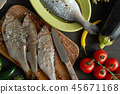 top view of a set of fresh, raw fish in various dishes and with vegetables on a black table 45671168