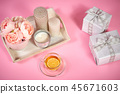 peonies, candles on a wooden tray, tea and gifts on a pink background 45671603