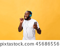 African American man with headphones listen and dance with music. Isolated on yellow background 45686556