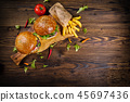 Delicious hamburgers with fries, served on wood 45697436
