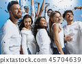 Group of cheerful joyful young people standing and celebrating together over blue background 45704639