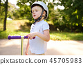 Toddler boy learning to ride scooter 45705983