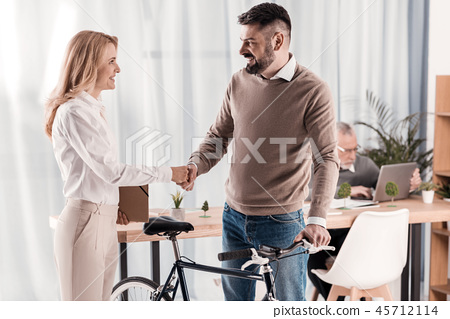 Exuberant woman shaking hands with her colleague 45712114