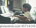 Boy playing with piano and Music Tablet at home 45714145