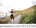 Young sporty woman runner in black activewear standing outside in nature, stretching. 45725706