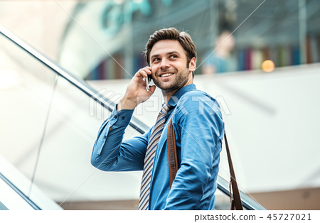 A young businessman going up escalator, talking on the phone. 45727021
