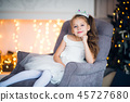 Pretty little girl sitting in the armchair. Magic and festive atmosphere. 45727680