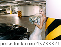 The bride is in the underground Parking near the black car 45733321