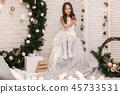 Pretty smiling girl near the Christmas wreath 45733531