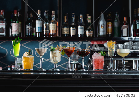 row of various colourfull alcoholic cocktails on a bar desk. Glasses of differen shapes 45750903