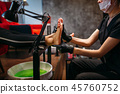 Pedicurist in black gloves rubs the cream 45760752