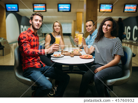 Friends drinks and eats pizza in bowling club 45760932
