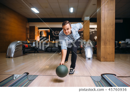 Male bowler throws ball on lane, front view 45760936