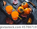 Ripe orange persimmon fruit and persimmon leaves in a brown plate on a black wooden table 45766719