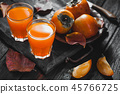 Ripe orange persimmon fruit and persimmon leaves in a brown plate on a black wooden table 45766725