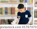 Boy using magnifying glass in library. 45767970