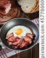 Slices of smoked bacon and fried egg in frying pan 45776660