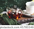 Hot tea in glass tea pot over green background 45785546