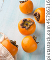 Ripe persimmons on turquoise background 45786316