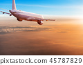 Commercial airplane flying above dramatic clouds. 45787829