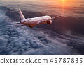 Commercial airplane flying above dramatic clouds. 45787835