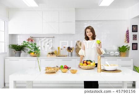 Modern housewife working in kitchen. 45790156