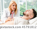 Woman Doctor and Male Patient in Hospital Office 45791812
