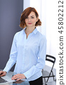 Young brunette business woman looks like a student girl working in office. Caucasian  girl standin 45802212