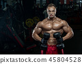handsome man with big muscles trains in the gym, e 45804528