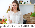 Young happy woman cooking in the kitchen. Healthy meal, lifestyle and culinary concepts. Good 45804707