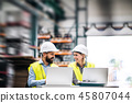 A portrait of an industrial man and woman engineer with laptop in a factory, working. 45807044