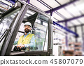 Mature industrial man engineer sitting in a forklift in a factory. 45807079