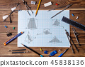 Graph paper with geometry pictures and student material on wooden table. 45838136
