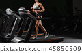 Pretty Latin young women working out in an elliptical trainer in 45850509